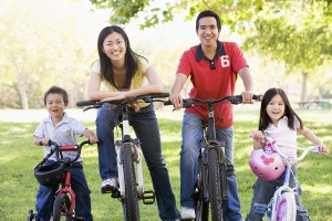 Families On Bikes Outdoors Smiling