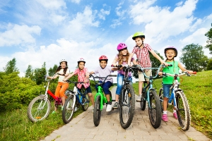 Happy kids in row wear colorful bike helmets